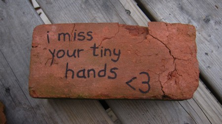 I miss your tiny hands, written on a brick